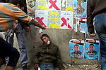A young man sprayed saline on protester slumped against a wall on Mohamed Mahmoud Street near Tahrir Square, Cairo, Egypt, Sunday, Nov. 20, 2011. Around 1500 people have been injured and 23 killed in the clashes ahead of Egypt's parliamentary election beginning on November 28.