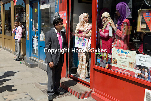 """Muslim women Brick Lane London wait for wedding guests to enter a resturant. The sign she holds reads """"No Money No Honey""""' a tradition in Bengali wedding for the brides relatives to tease the groom into giving a small gift of money, a dowry, once thats done the ribbon is cut and he is allowed in."""
