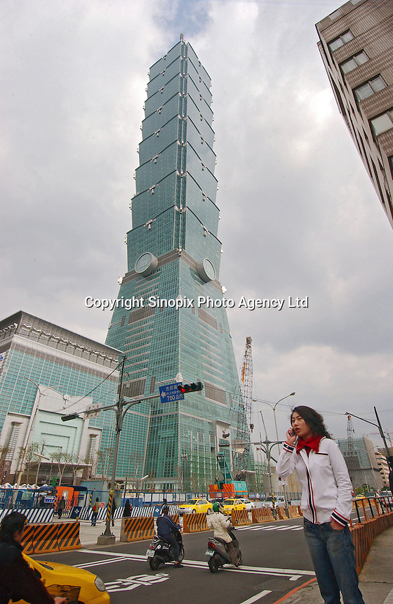 Traffic and pedestrians pass by the base of Taipei 101 tower in Taipei, Taiwan. At 508m, the skyscraper is currently the world's tallest building..