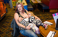 A mother tandem feeds her two children, one about one about twelve weeks and one about 28 months old, at a sling meet held in the family restaurant and play area in a pub.<br /> Lancashire, England, UK<br /> <br /> Date Taken:<br /> 07-01-2015<br /> <br /> © Paul Carter / wdiip.co.uk