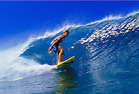 A surfer rides a beautiful blue wave at Pupukea beach, North shore Oahu.