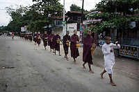 A group of novice monks on their early morning alms round, on the outskirts of Mandalay.