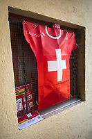 """Switzerland. Canton Ticino. Vezia. A plastic shirt of the Swiss Football team and a prevention poster again Coronavirusalso called Covid-19) are fixed on a window inside the courtyard of a private house. The Swiss Football Association (SFV) has for sponsor the multi-national investment bank and financial services company Credit Suisse. The Coronavirus poster explains how to prevent from getting the disease. The measures are: Keep your distance, wash your hands thoroughly, avoid shaking hands, cough and sneeze into a tissue or the crook of your arm, stay at home if you have fever, always call ahead before going to the doctor's or the emergency department. Due to the spread of the coronavirus, the Federal Council has categorised the situation in the country as """"extraordinary"""". It has issued a recommendation to all citizens to stay at home, especially the sick and the elderly. The Federal Council (German: Bundesrat, French: Conseil fédéral, Italian: Consiglio federale, Romansh: Cussegl federal) is the seven-member executive council that constitutes the federal government of the Swiss Confederation. From March 16 the government ramped up its response to the widening pandemic, ordering the closure of bars, restaurants, sports facilities and cultural spaces. Only businesses providing essential goods to the population – such as grocery stores, bakeries and pharmacies – are to remain open. Vezia is a municipality in the district of Lugano. <br /> The flag of Switzerland displays a white cross in the centre of a square red field. The white cross is known as the Swiss cross. Credit Suisse Group AG is a global wealth manager, investment bank and financial services company founded and based in Switzerland. 27.03.2020 © 2020 Didier Ruef"""