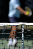 a net with a tennis player preparing to serve in the background