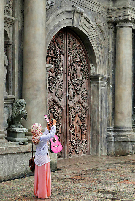 Muslim women taken a selfie outside the San Augustin Church and holding a colorful Guitar, Manila, Philippines
