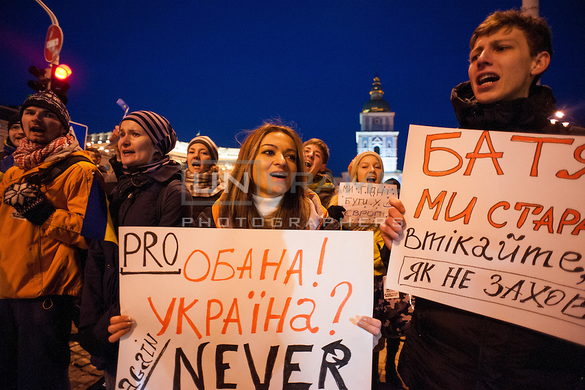 Demonstrators holding anti government banners  in front of the nearby Mykhailiv monastery where people regathered  to continue the  protest  after the violent repression  on main square performed by the riot police, Kiev.