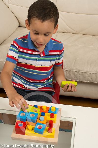 3 year old boy playing with shape and peg wooden puzzle