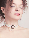 Closeup of young beautiful woman face wearing a pink rose lace choker on her neck Image © MaximImages, License at https://www.maximimages.com