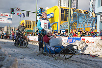Paige Drobny and team leave the ceremonial start line with an Iditarider at 4th Avenue and D street in downtown Anchorage, Alaska during the 2015 Iditarod race. Photo by Jim Kohl/IditarodPhotos.com