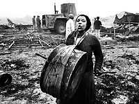 A resident of Bloekombos squatter camp wails and beats a drum as white council workers, guarded by riot police, bulldoze about 35 shacks during a dawn raid in the dying days of apartheid.