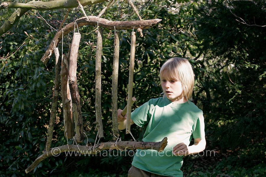 Kinder basteln Klangspiel aus Ästen, Junge macht Musik am fertigen Klangspiel