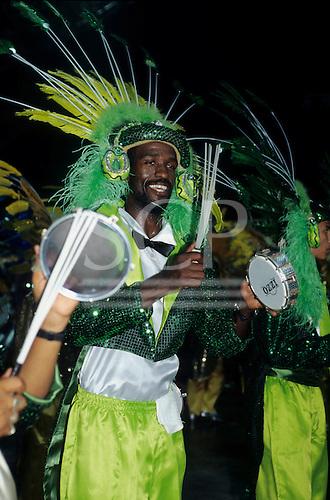Rio de Janeiro, Brazil. Carnival: samba school musicians in green costumes playing pandeiro.