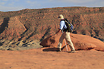 Man hiking near Delicate Arch in Arches National Park, Moab, Utah, USA. .  John leads hiking and photo tours throughout Colorado. .  John offers private photo tours in Arches National Park and throughout Utah and Colorado. Year-round.
