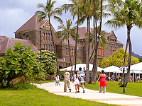 A family and other visitors walk towards the venerable Hawaiian Hall at the Bernice Pauahi Bishop Museum, a major repository of Hawaiian culture. A planetarium and science center with recreated volcano are also on the grounds.