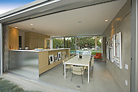 Diningroom and kitchen are seen from outside through open movable aluminum walls of mid-century modernism house
