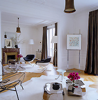 General view of the large, elegant living room with parquet flooring and furnished with various designer pieces