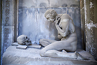 Picture and image of the stone sculpture of a nude looking at a skull on a crucifix.  Sculpted in an art Nouveau style the sculture is a reminder that beauty and life is transient. The Lavarello tomb sculpted by Demetrio Paernio 1914. The monumental tombs of the Staglieno Monumental Cemetery, Genoa, Italy