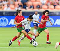 HOUSTON, TX - JUNE 10: Joana Marchao #5 of Portugal attempts to strip the ball from Christen Press #23 of the United States with Dolores Silva #14 of Portugal running along side during a game between Portugal and USWNT at BBVA Stadium on June 10, 2021 in Houston, Texas.