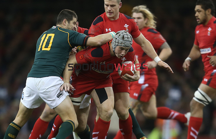 Wales center Jonathan Davies tries to slip past Springok outside half Morne Steyn.<br /> <br /> 2013 Dove Men Series<br /> Wales v South Africa<br /> Millennium Stadium<br /> 09.11.13<br /> ©Steve Pope-Sportingwales
