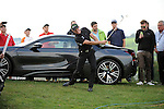 ISPS Handa Wales Open Golf final day at the Celtic Manor Resort in Newport, UK. :  Jamie Donaldson of Wales gets his ball out of the rough alongside the 18th green. His ball landed alongside an expensive BMW car that was on display.