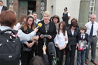 Pictured: Detective Constable for South Wales Police Charmaine Kinson (C) reads a statement on behalf of the family of tragic teen Rebeca Aylward, her mother Sonia is 3rd R  with her other daughter and son Jack who is holding a picture of Rebecca, standing outside Swansea Crown Court. Wednesday 27 July 2011<br /> Re: The jury on the trial of 17-year-old Joshua Davies who denies murdering his 15 year old ex-girlfriend Rebecca Aylward over an alleged bet for a free breakfast has found him guilty at Swansea Crown court.<br /> Rebecca was found dead in woods in Aberkenfig, near Bridgend, south Wales, in October 2010.