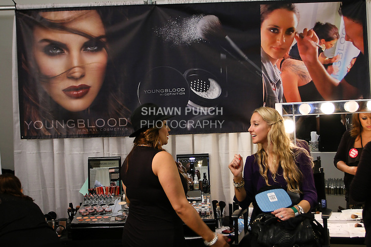 Youngblood Mineral makup artist talks with patron, at the Makeup Show NYC, May 15 2011.