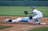 Sean Bouchard (5) of the UCLA Bruins takes a throw at first base while Tyler Lynn (20) of the North Carolina Tar Heels dives back to the bag during a game at Jackie Robinson Stadium on February 20, 2016 in Los Angeles, California. UCLA defeated North Carolina, 6-5. (Larry Goren/Four Seam Images)