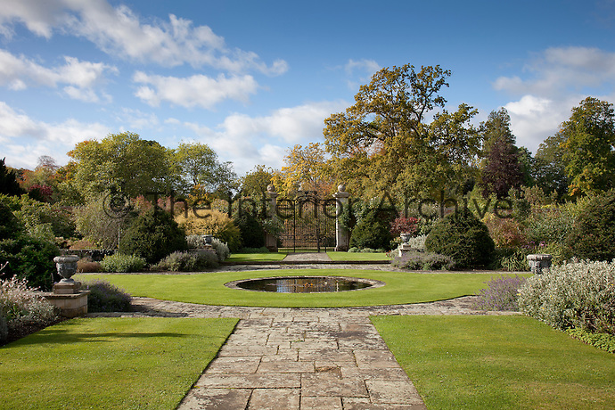 A circular lawn surrounds a pond in the garden, approached by a paved path