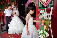Zeng Zhongzhong (left) and Jiang Xiaoxiao stand at the entrance to a banqueting suite, ready to welcome guests to their weddingreception. Next to them a bridesmaid reaches out to touch a humorous picture of the couple, dressed as Cultural Revolution era Red Guards. Able to seat up to 5,000 people at one sitting, The West Lake Restaurant is the biggest Chinese restaurant in the world. Each week its diners, who staff are taught are 'the bringers of good fortune', devour 700 chickens, 200 snakes, 1,200 kgs of pork and 1,000 kgs of chillis. Its 300 chefs cook in five kitchens and its staff total more than 1,000.It is fully booked most nights.