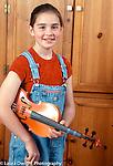 8 year old girl portrait closeup holding musical instrument viola vertical Caucasian