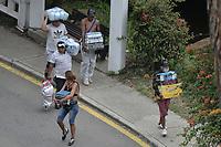CALI - COLOMBIA, 28-04-2021: Un grupo de personas llevan el prodcuto del saqueo de un supermercado en el oeste de la ciudad de Cali durante la jornada del Paro nacional en Colombia hoy, 28 abril de 2021, para protestar por la reforma tributaria que adelanta el gobierno de Ivan Duque además de la precaria situación social y económica que vive Colombia. El paro fue convocado por sindicatos, organizaciones sociales, estudiantes y la oposición. / A group of people carry the prodcut of the looting of a supermarket in the west of the city of Cali during the day of the national strike in Colombia today, April 28, 2021, to protest the tax reform carried out by the government of Ivan Duque in addition to the precarious social and economic situation that Colombia is experiencing. The strike was called by unions, social organizations, students and the opposition in Colombia. Photo: VizzorImage / Gabriel Aponte / Staff