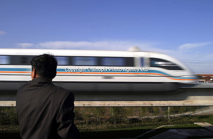 QS031123Shanghai003 20031123  SHANGHAI, CHINA: A Shanghai Transrapid magnetic levitation train speeds past a spectator in Shanghai, China 23 November 2003. Able to reach a top speed of 430 kilometers per hour, the Transrapid completes the 30 kilometers journey between the Pudong International Airport and the  Longyang Metro Station in just over 7 minutes. Still under its testing phase and carrying tourists on a wekend-only basis, the line will be in full operation early next year and expects to carry 10 million passengers per year by 2005.