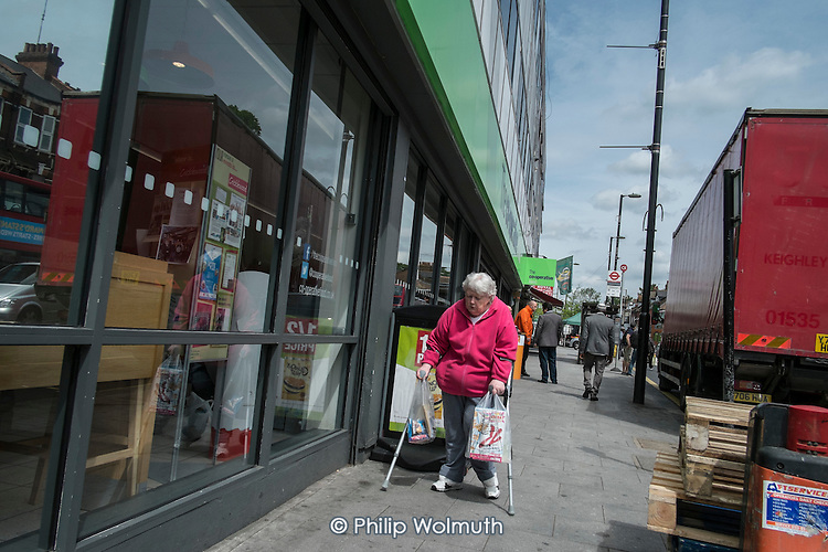 Woman with crutches and shopping bags outside Cricklewood Co-op store, London.