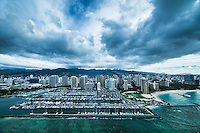 An aerial view of a cloudy sky over Ala Wai Harbor, the Hilton Hawaiian Village's lagoon and Kahanamoku Beach, Waikiki, O'ahu.