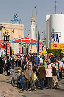 Tripoli, Libya, North Africa - Libyan Men, Women, Families at International Trade Fair.  Clothing Styles.  Minaret in Background.