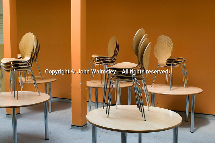 Chairs on tables after lunchtime, state secondary school.