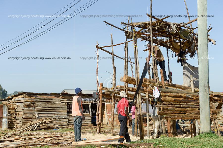 TANZANIA, Tarime, local sawmill , worker saw tree trunks manually with crosscut saw  / lokales Saegewerk, Arbeiter saegen Baumstaemme mit Zugsaege
