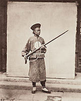 BNPS.co.uk (01202 558833)<br /> Pic: ForumAuctions/BNPS<br /> <br /> Pictured: A young man shows off a massive gun.<br /> <br /> Rarely seen 150 year old photos taken by one of the first British photographers to explore China have emerged for sale for £20,000.<br /> <br /> Scotsman John Thomson (1837-1921) travelled to the Far East in 1868 and established a studio in Hong Kong, using it as a base to explore remote parts of the vast country for the next four years, photographing landmarks, scenery and the native population.<br /> <br /> In many cases, he was the first Westerner the people he photographed had encountered.<br /> <br /> One striking image shows a prisoner in chains with a head poking through a board covered in Chinese symbols, perhaps listing his misdemeanours. In another, a man poses next to a giant camel statue in the grounds around the Ming tombs of the Forbidden City.<br /> <br /> Almost 100 of his photos feature in a rare first edition of 'Thomson Illustrations of China and Its People' (1873), which is going under the hammer with London-based Forum Auctions.
