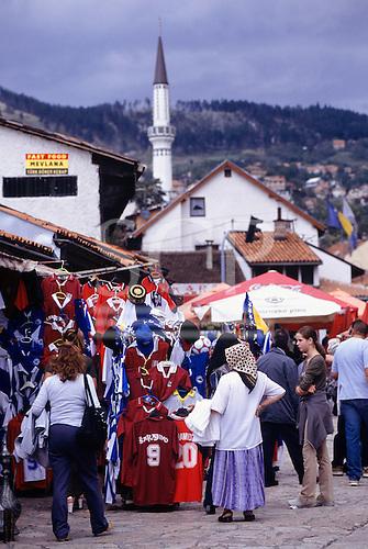 Sarajevo, Bosnia and Herzegovina. The arab quarter (Bascarsija); market; stall selling clothes (t-shirts); minaret.