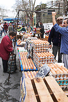 A market stall street market merchant selling eggs in egg cartons, and old lady shopping Montevideo, Uruguay, South America