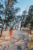 Honduras, Roatan Island, Fantasy Island Resort, Caribbean. Woman walking on the beach amidst the trees.