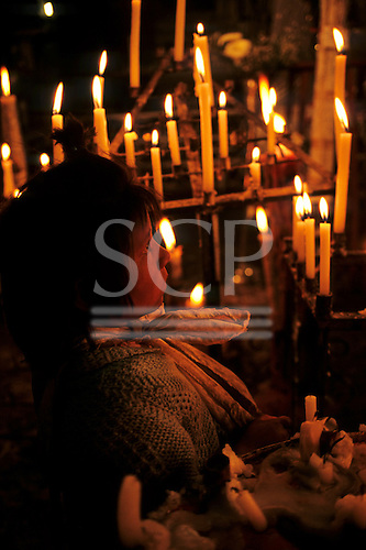 Peru. Young girl and votive candles in a church.