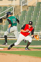 First baseman Ian Gac #33 of the Kannapolis Intimidators comes off the bag to field a throw as Ryan Lollis #22 of the Augusta GreenJackets hustles down the line at Fieldcrest Cannon Stadium June 24, 2010, in Kannapolis, North Carolina.  Photo by Brian Westerholt / Four Seam Images