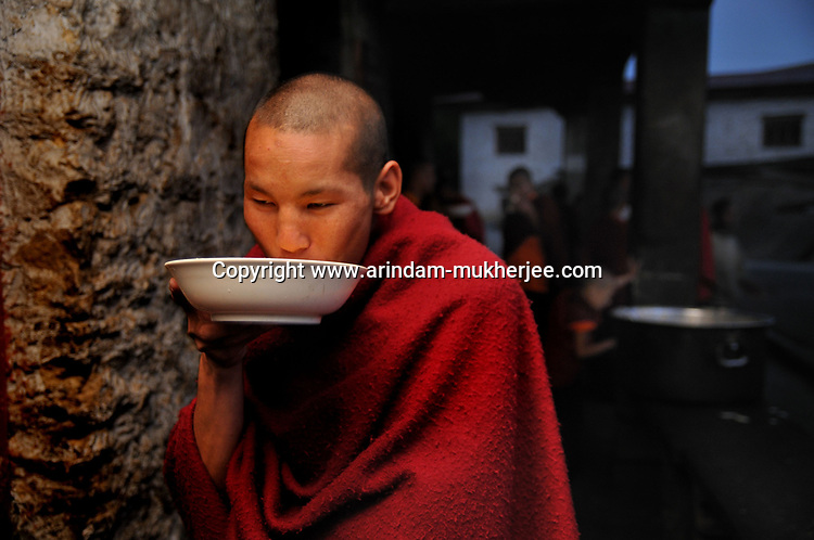 A Lama, who is a student at Kharchhu Monastry (which is a buddhist school and college) having his dinner in the evening. These lamas lead a very modest life and have simple food three times a day. Arindam Mukherjee
