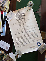 BNPS.co.uk (01202 558833)<br /> Pic: PhilYeomans/BNPS<br /> <br /> Thomas's Royal Warrant sold for 3200 pounds.<br /> <br /> A remarkable 'timewarp' archive amassed by a dressmaker to the Queen has sold for over £100,000.<br /> <br /> The late Ian Thomas meticulously kept his fashion designs, letters, cards and photographs relating to the Queen at his home that was more like a museum. <br /> <br /> He helped design the Queen's coronation gown in 1953 as well as the powder blue outfit she wore for Charles and Diana's wedding in 1981.<br /> <br /> The lifelong bachelor passed away in 1993 and left his home and its contents to a florist he had been good friends with for 25 years.<br /> <br /> After she died in 2015 the property was inherited by a relative who also knew Mr Thomas well.<br /> <br /> She has now sold the contents at auction.