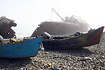 TWO PANGA BOATS on the BEACH WITH SHIP WRECKED BOAT FLOATING OFF the MEXICAN COAST in the BACKGROUND