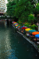 People eating at a restaurant on the riverwalk, River Walk Paseo del Rio, in San Antonio, South of Texas, USA, United States. There are a lot of restaurants along the river and the people can eat under colorful umbrellas. The best way to discover the city of San Antonio is to sail on the River with a motorboat. (No MR)