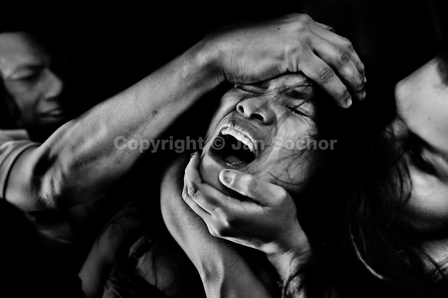 A Colombian girl screams of pain and fear while being allegedly possessed by demons during the exorcism ritual performed at a house church in Bogota, Colombia, 28 January 2013. Hundreds of Christian belivers, joined in nameless groups, gather every week in unmarked home churches dispersed in the city outskirts, to carry out prayers of liberation and exorcism. Community members and their religious activities are usually conducted by a charismatic pastor or preacher. Using either non-contactive methods (reading religous formulas from bible, displaying Christian symbols and icons) or rough body-pressure-points techniques and forced burping, a leading pastor commands the supposed evil spirit, which is generally believed to come from witchcraft, to depart a person's mind and body. The demon's expulsion often consists of multiple rites and may last for several months.