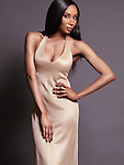 Fashion portrait of a beautiful african american woman wearing a gold dress. Isolated on gray studio background. Image © MaximImages, License at https://www.maximimages.com