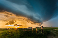 Supercell thunderstorm above hay bales during sunset in Montana, May 18, 2014